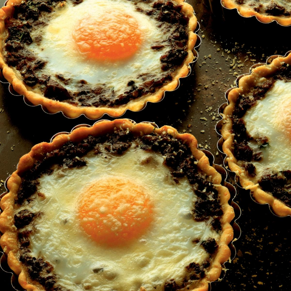 Winter baked eggs in wild mushroom tartlets